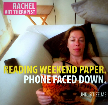 Reading Weekend Paper. Phone Faced Down.